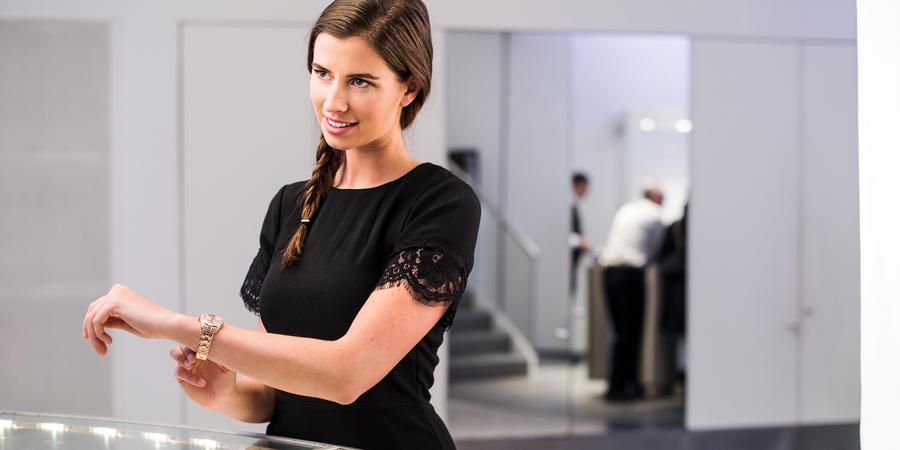 Een vrouw met horloge staat voor de toonbank in een juwelierszaak.