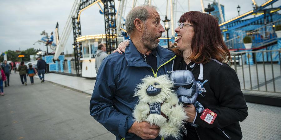 Man en vrouw kijken elkaar van dichtbij aan, gewonnen knuffels in de hand