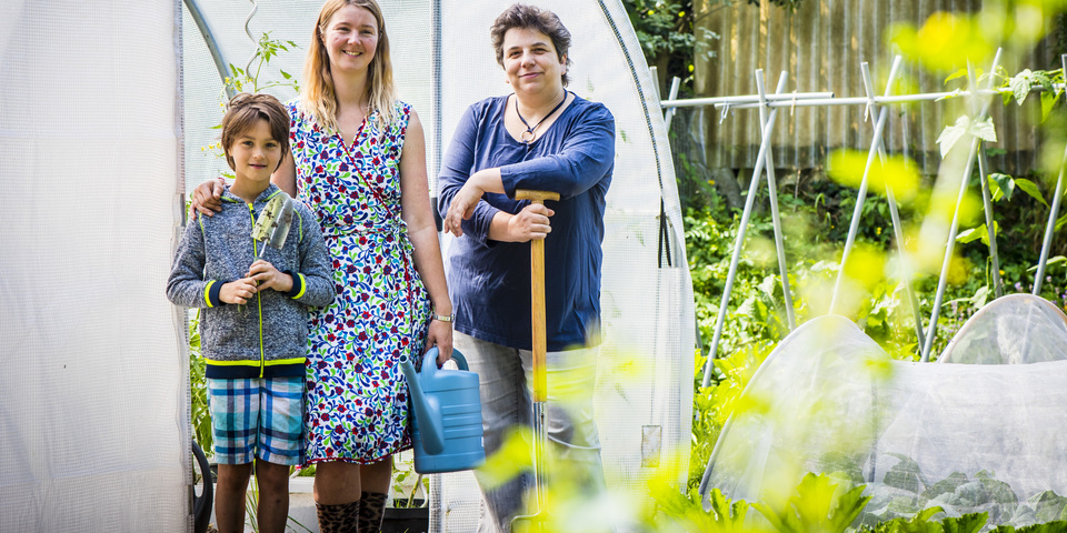 Drie tuiniers van Samentuin staan trots voor hun serre