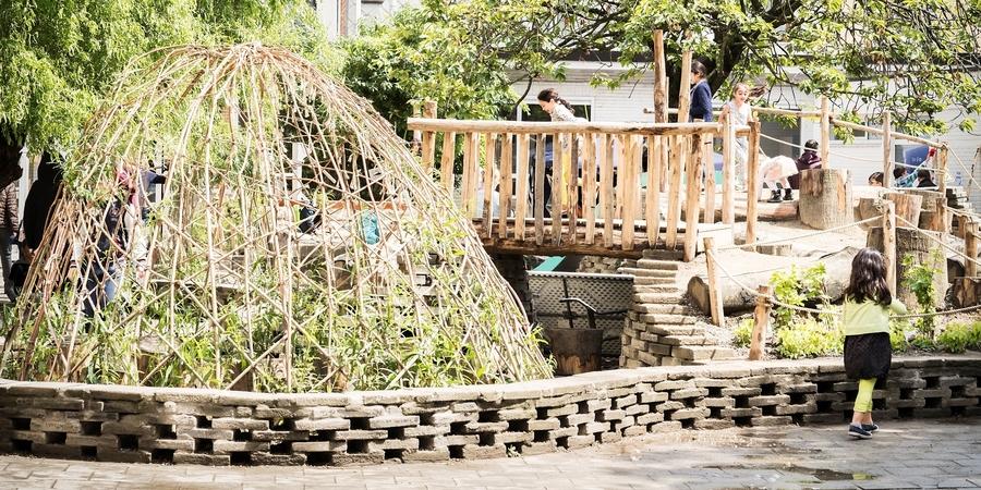 De natuurspeelplaats van stedelijke basisschool De Bever met een muurtje gebouwd uit dals.