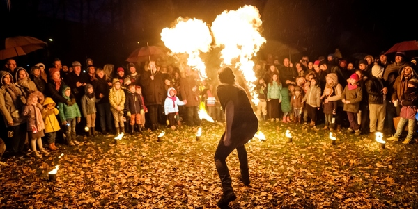 Een vuurartiest zorgt voor een grote vuurbal, gadegeslagen door tientallen jonge en volwassen toeschouwers tijdens een vorige editie van de Lichtjesstoet