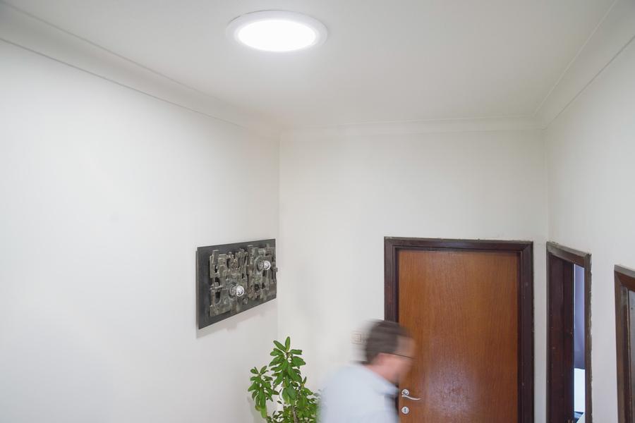 Iemand loopt door de hal, in het plafond is een ronde opening, waardoor daglicht naar binnen straalt.