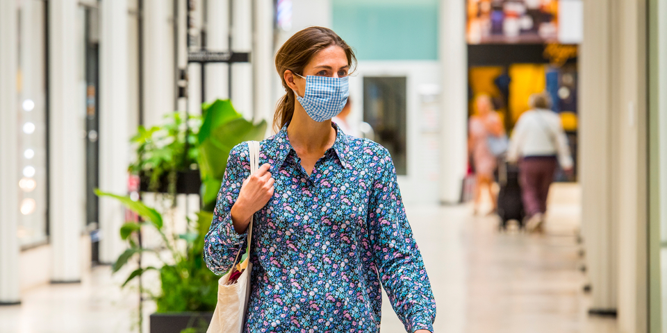 Vrouw met een mondmasker en schoudertas is aan het winkelen.