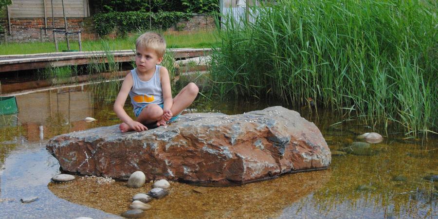 Jongen zit op steen in het water
