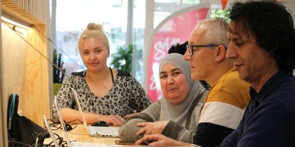 Driss van Buurtwerk Borgerbaan helpt bezoekers met de computer werken.