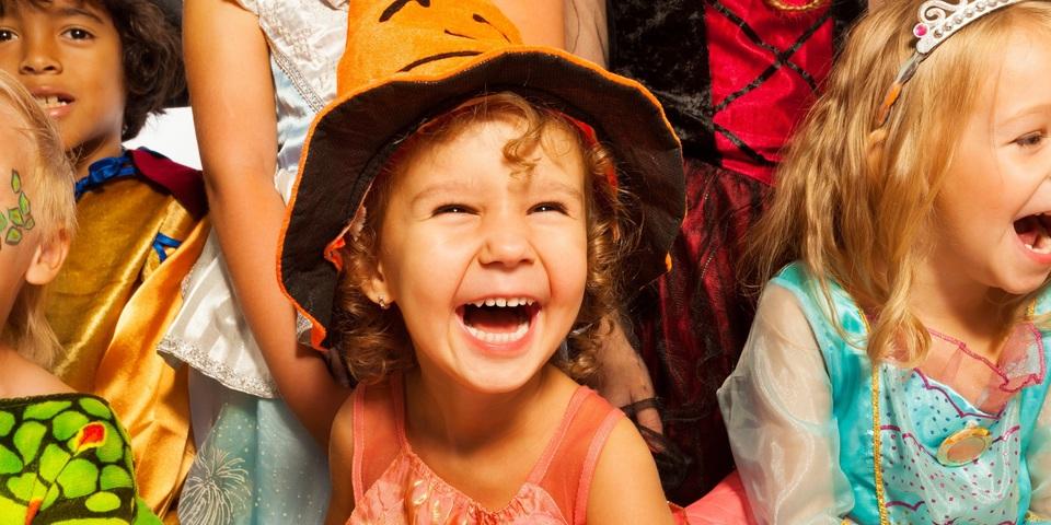 Jong meisje met heksenhoek lacht naar de camera, en is omringd door andere kinderen in verschillende verkleedkostuums.