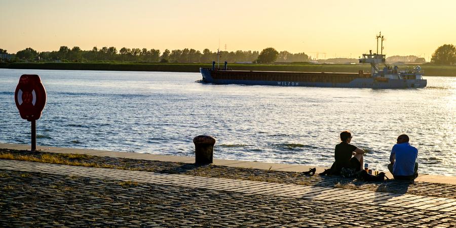 Een vrouw en een man zitten op de kaaimuur. In de achtergrond vaart een binnenschip over de Schelde.
