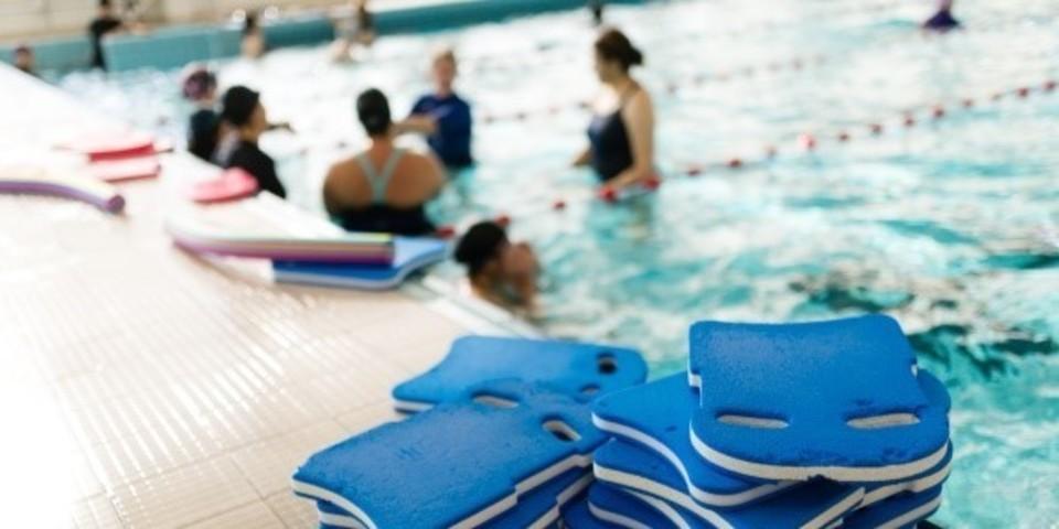 Zwemplankjes liggen op de rand van het zwembad. In de verte staat een groepje zwemmers met hun lesgever.