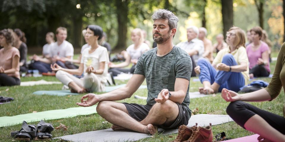 Een groep mensen volgt een yogales in het park. Een man zit neer in yogahouding in het midden van de groep.