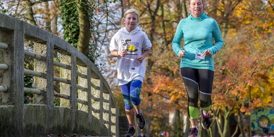 Moeder en dochter die samen lopen over een brug in park Sorghvliedt