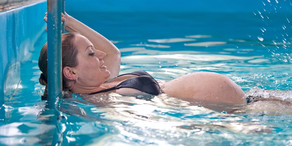 Een zwangere vrouw ligt ontspannen in het zwembad