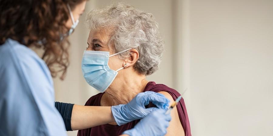 Oudere dame krijgt een vaccin in de arm
