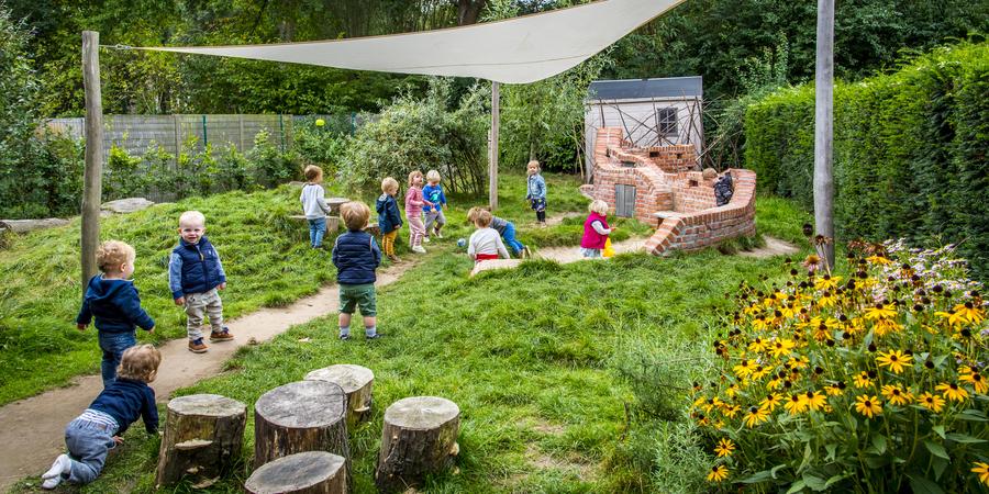 Kinderen spelen in de vernieuwde avontuurlijke tuin van kinderdagverblijf Het Sprookjesland