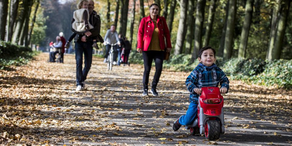 Ouders en hun kinderen wandelen in een park.