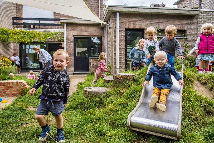 Kinderen glijden van de glijbaan aan de speelheuvel