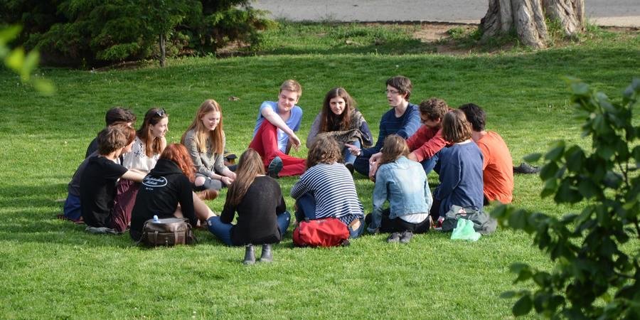 Een groep komt op het gras bijeen om te kletsen