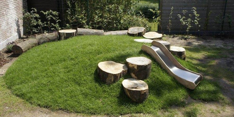 De speelheuvel met boomstammetjes en glijbaan in kinderdagverblijf Sprookjesland