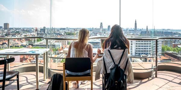 Twee studenten studeren in het MAS met zicht op Antwerpen, de kathedraal en de boerentoren in de verte