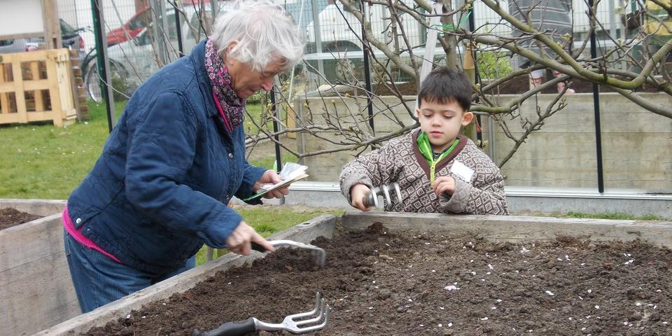 Bezoekers van het dienstencentrum en schoolkinderen tuinieren samen in de Pottentuin Kronenburg