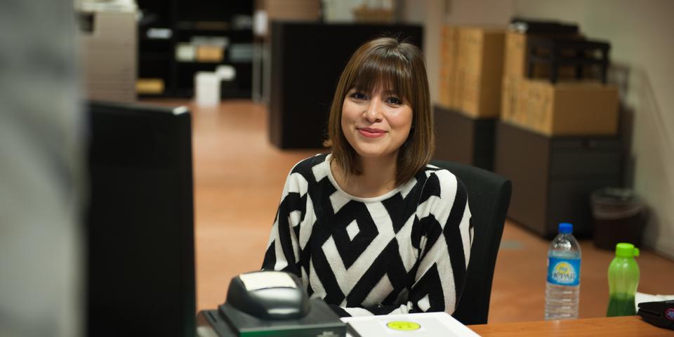 student werkt aan een bureau en lacht in de camera