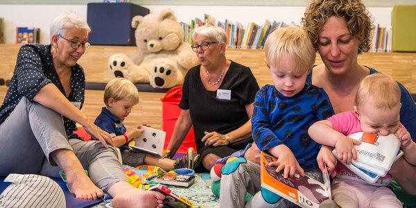 Mama's lezen voor in een bibhoekje in bibliotheek Bist