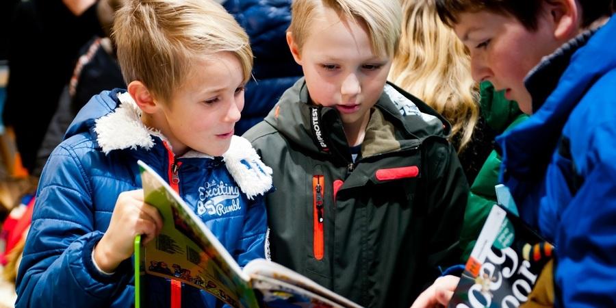 Leerlingen bekijken boeken in de bibbus