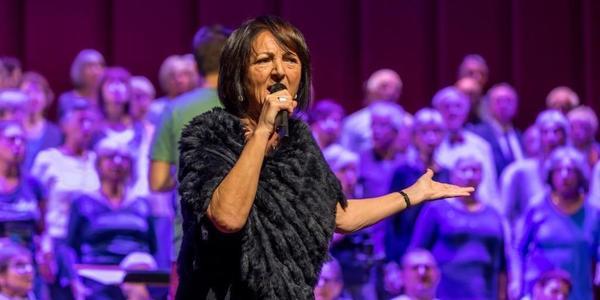 Dame zingt op podium tijdens Jong van Hart met koor op achtergrond