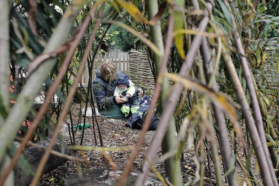 Begeleider en peuter in regenpak zitten buiten op de boomschors