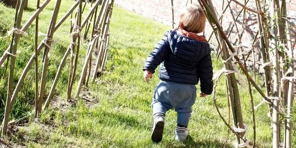 Jongen loopt door wilgentunnel in KDV Brabbel