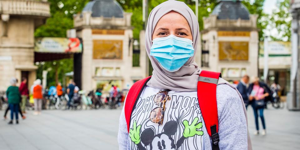 Een vrouw met mondmasker die voor de Antwerpse Zoo staat, kijkt in de camera. Op de achtergrond staan verschillende mensen voor de ingang van de dierentuin.