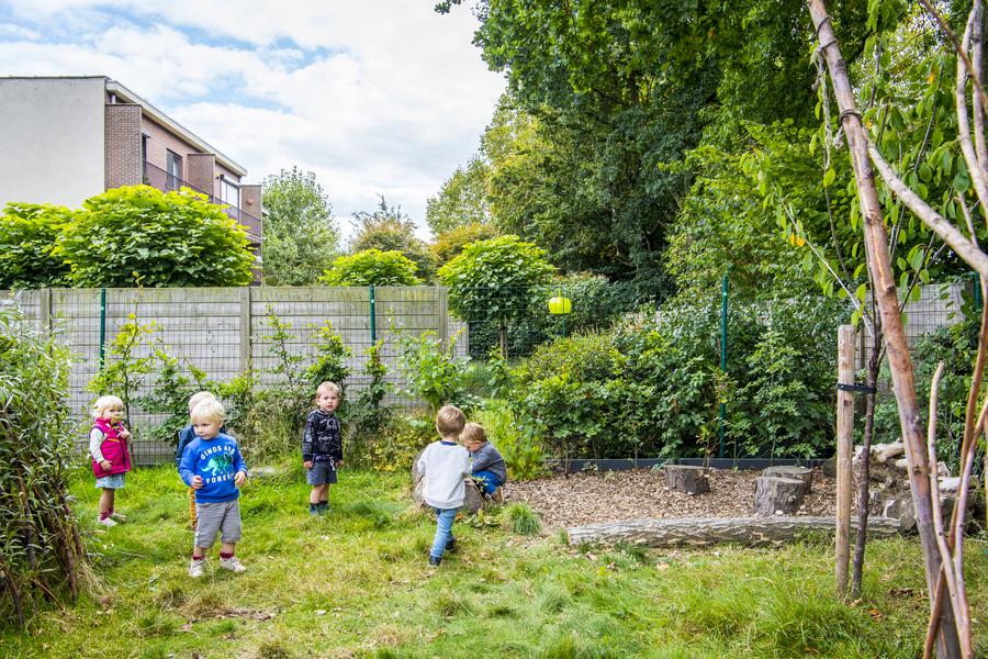 Kinderen spelen bij de houtsnipperzone met boomstammetjes