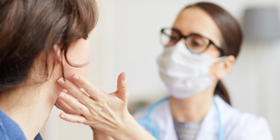 Huisdokter voelt aan keel van patiënt