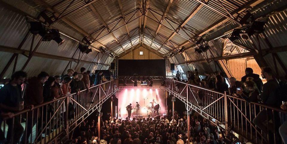 Bezoekers luisteren naar een concert in een hangar