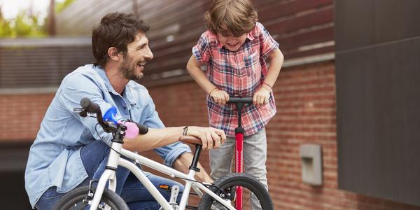 Volwassene en kind aan de slag met fietspomp.