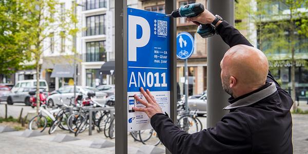 Technieker vervangt sticker van parkeerinfobord