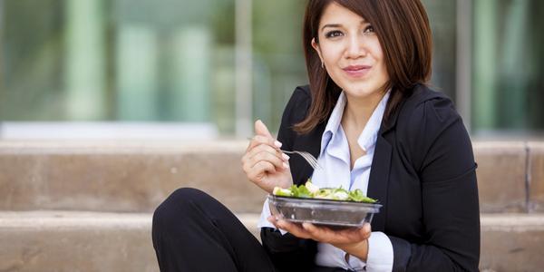 Vrouw eet buiten haar slaatje op