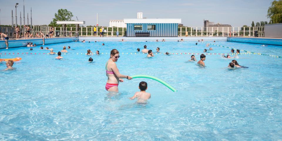 Tientallen mensen zwemmen en maken plezier in openluchtzwembad De Molen.