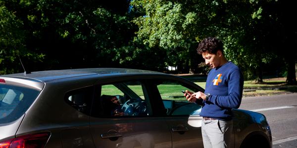 Man staat naast auto en gebruikt zijn gsm