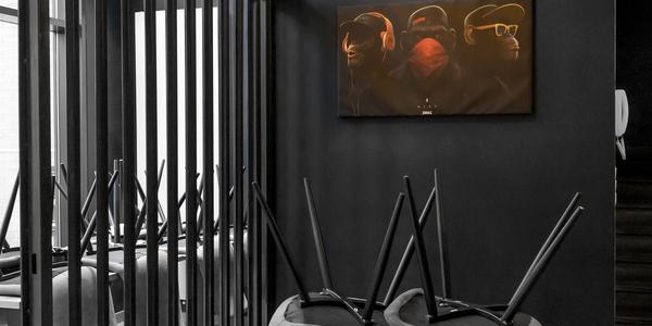 Zwart wit foto gesloten horecazaak met schilderij horen-zien-zwijgen in kleuraccent