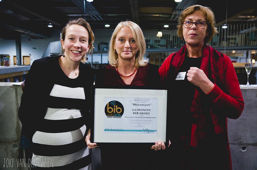 Medewerkers van het Taalpunt Nederlands poseren met de bronzen Bib Web Award.