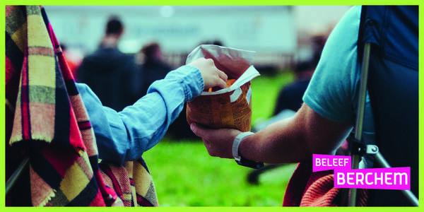 Twee mensen delen een pak chips terwijl ze in het gras naar een film kijken.