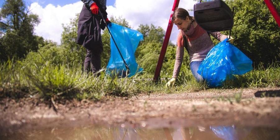 Twee mensen met blauwe vuilniszakken ruimen zwerfvuil op langs een rivier.