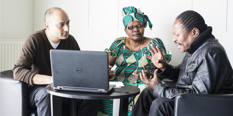 Drie leden van een vereniging vergaderen.