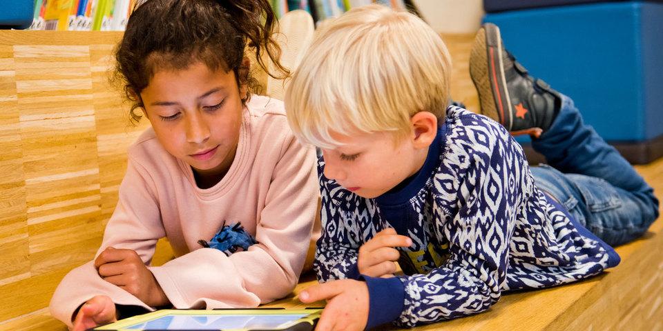 Twee kinderen lezen Fundels op een tablet van de bib