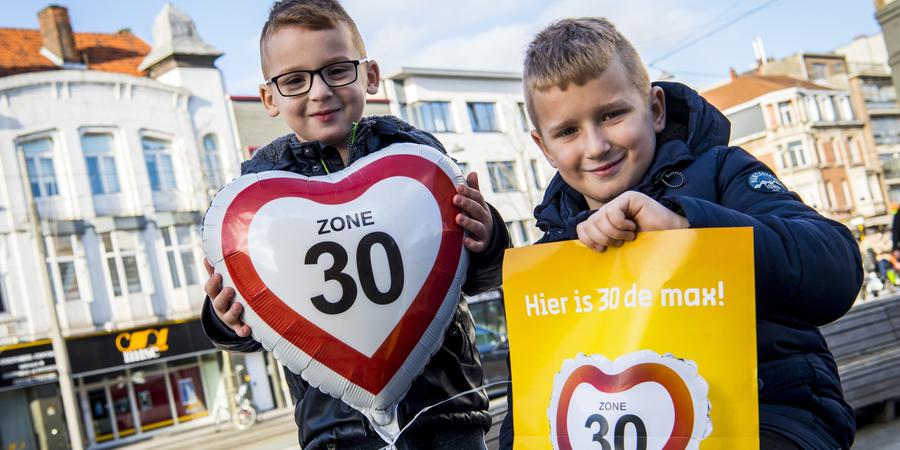 Twee jongens poseren met een ballon en een affiche waarop 'zone 30' staat.