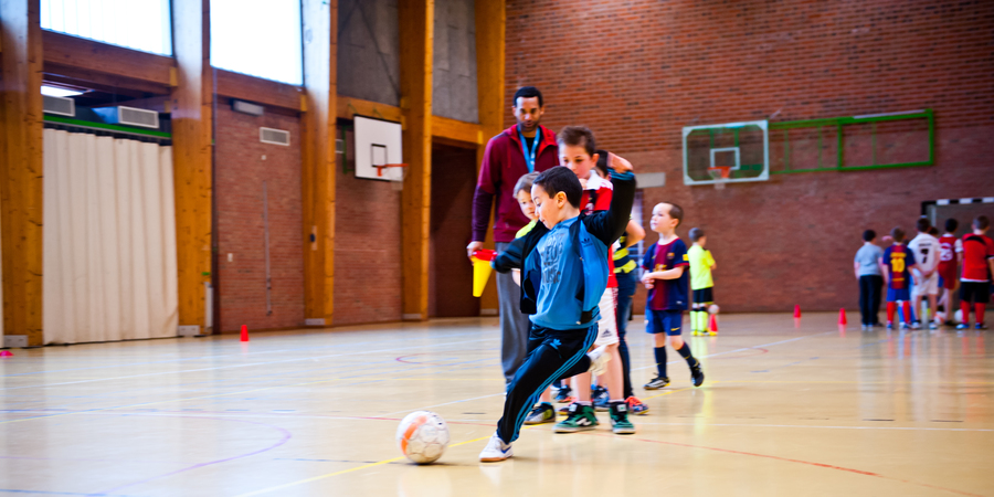 Kinderen op een voetbaltraining in een sporthal
