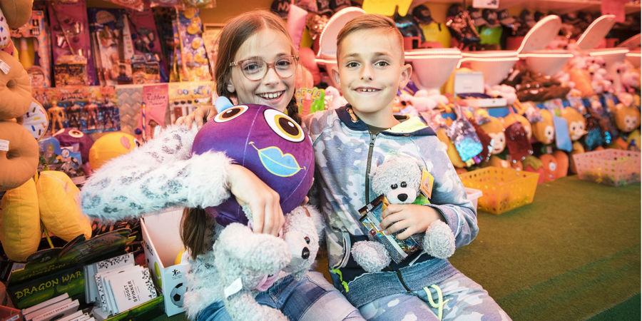 Meisje en jongetje poseren blij met hun pas gewonnen knuffels aan een kraam