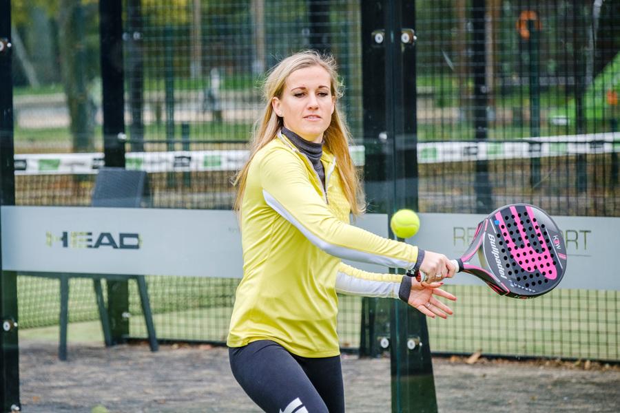 Een blonde vrouw tijdens een padelwedstrijd (padel is een mix tussen tennis en squash)