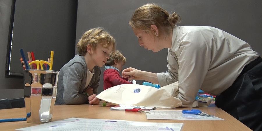 Een jongen krijgt uitleg van een begeleider in een workshop.