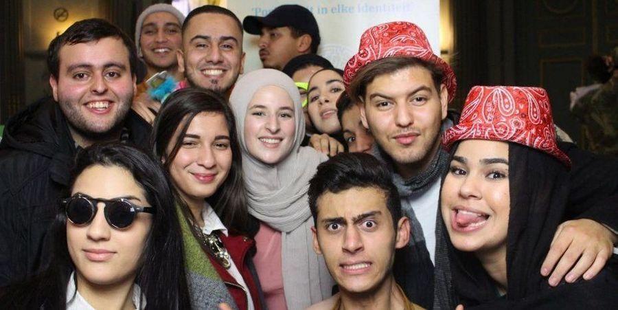 Een dozijn jongeren met een migratieachtergrond poseert voor de camera.